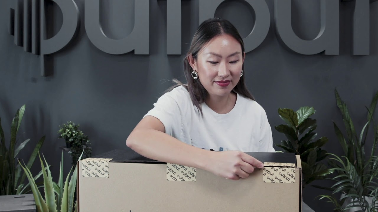 Woman unboxing Output Frontier studio monitor speakers