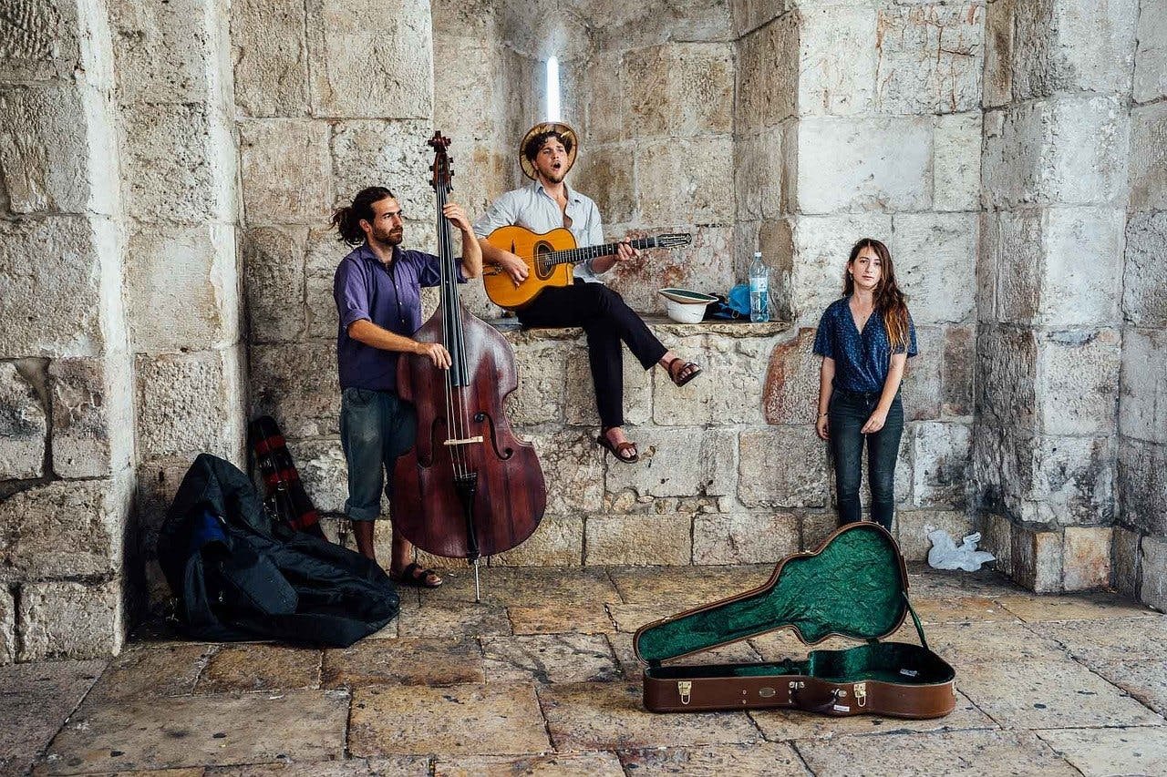 A group of musicians including a bassist, guitarist, and singer, relax in an old stone building.