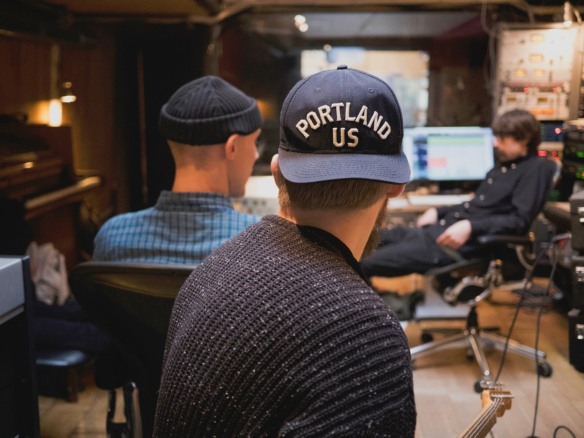 Three music producers collaborating in a studio surrounded by instruments.