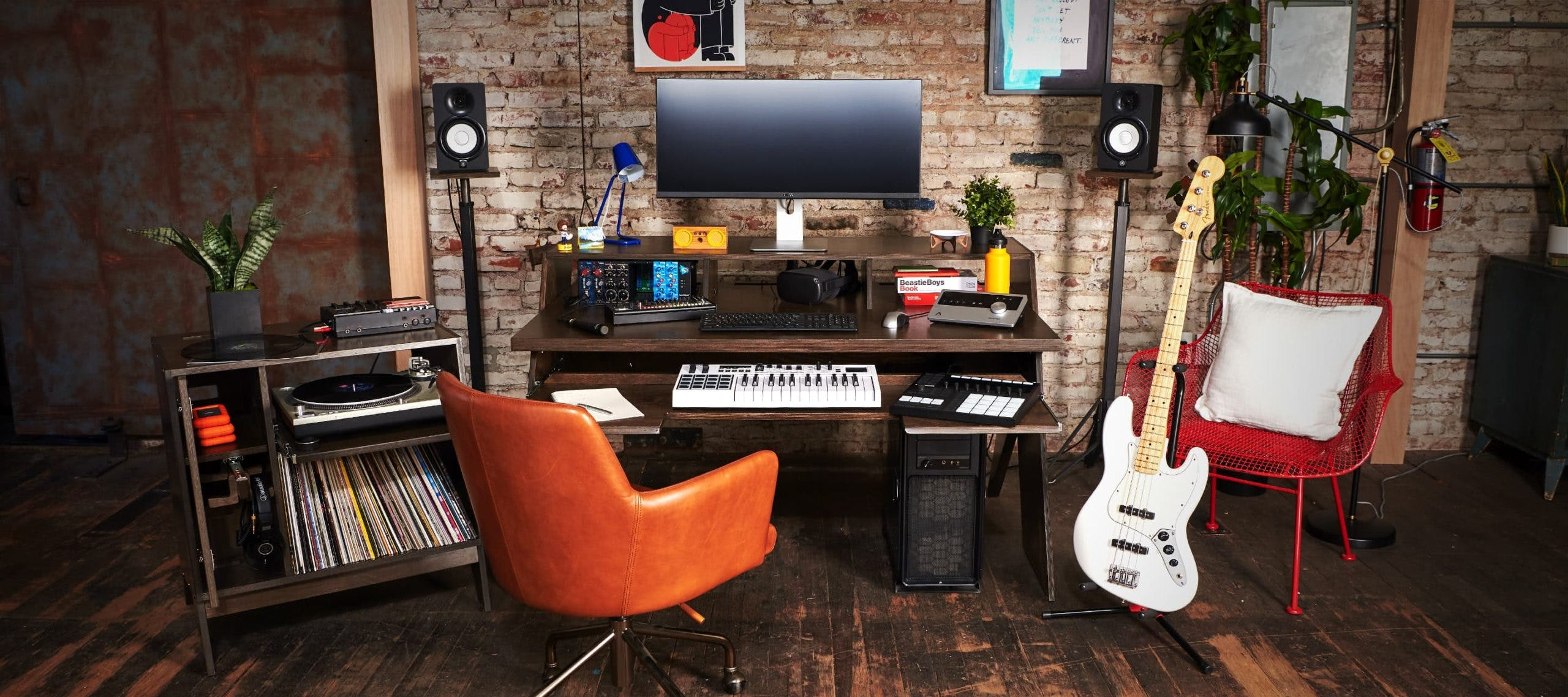 Studio setup in room with brown Output Platform desk, brown Output sidecar accessory, white Fender guitar, studio monitors, and colorful home accessories.