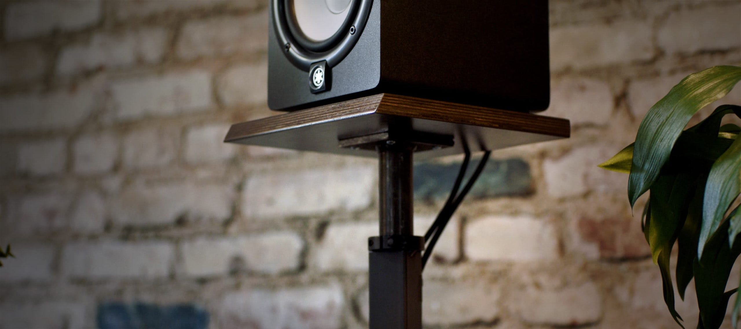 Yamaha HS8 Studio Monitors sitting on top of brown Output speaker stands.