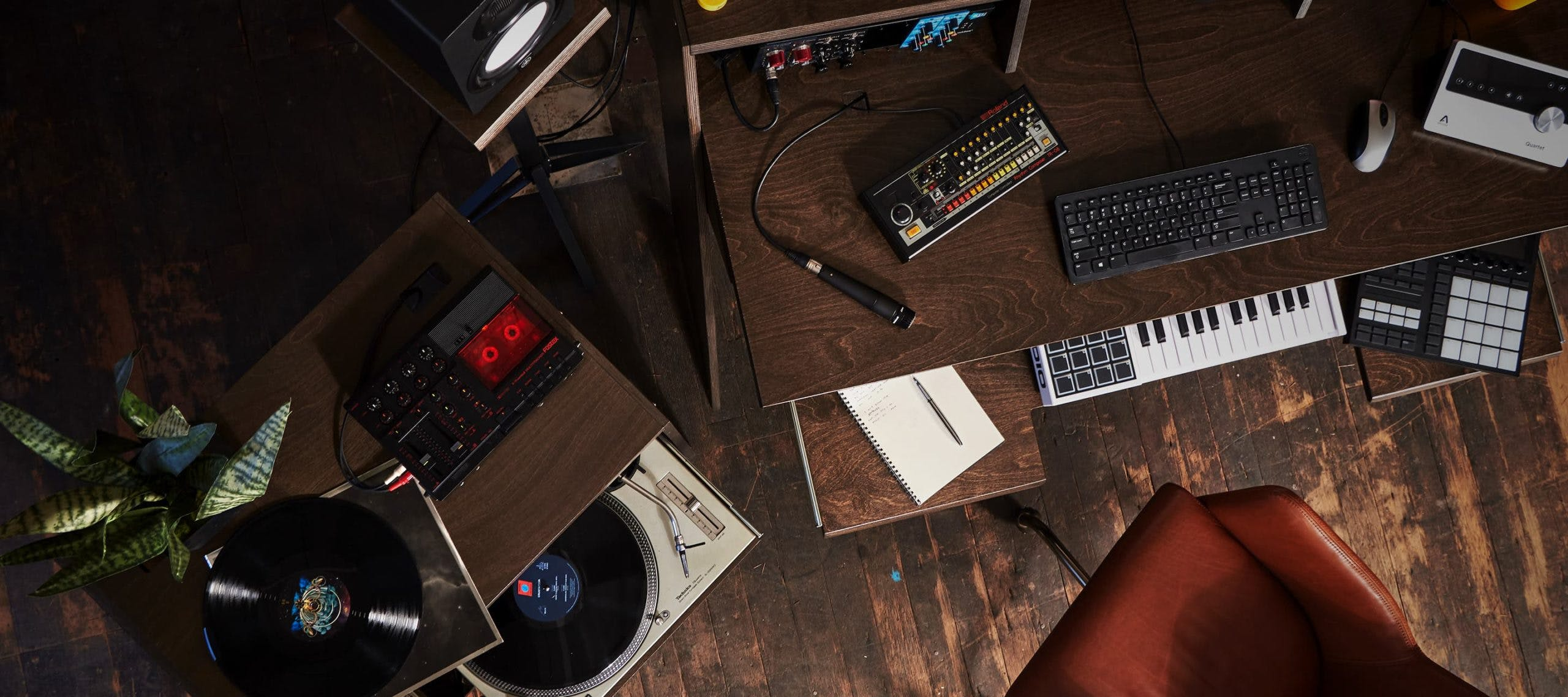 Aerial view of studio setup with brown Output Platform desk, brown Output Sidecar accessory holding turntable, MIDI controller, and keyboard.