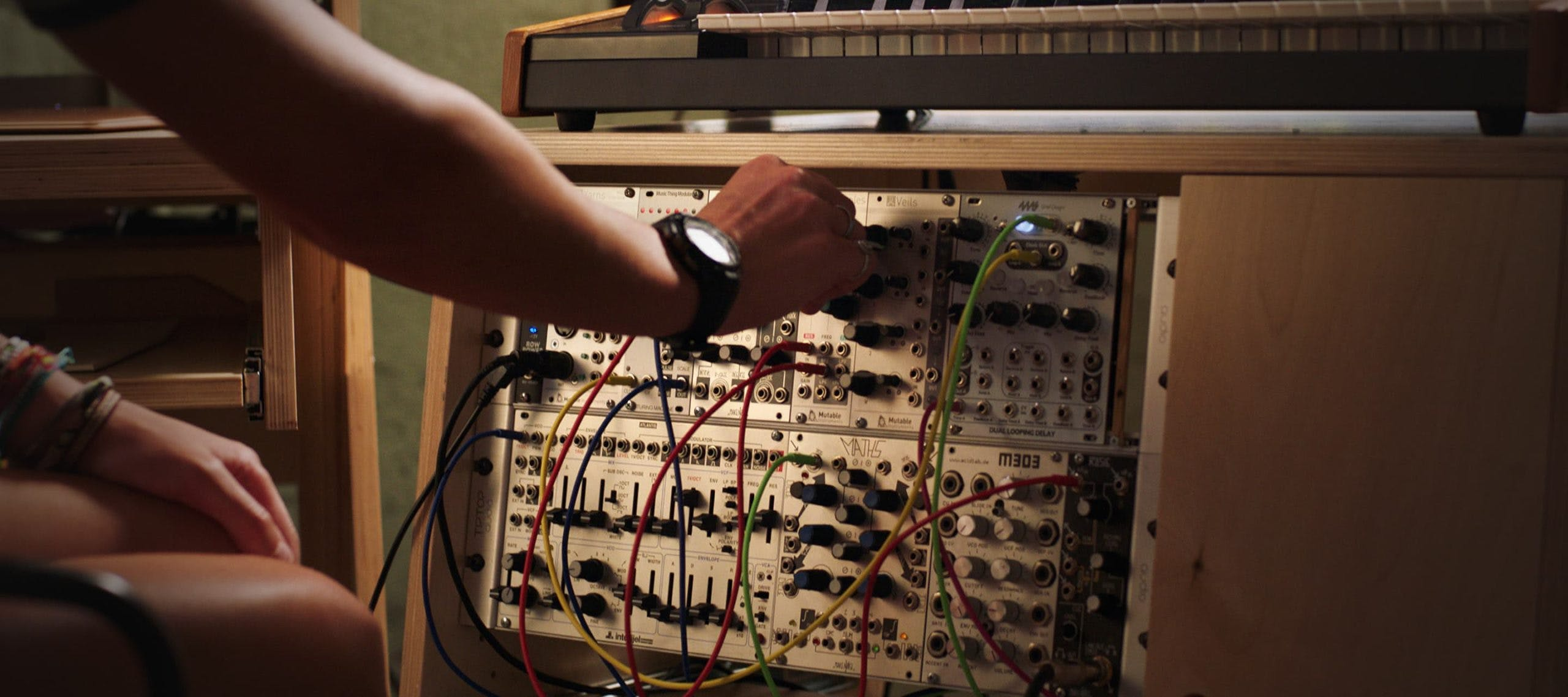 Person using analog synth held in natural color Output Sidecar accessory.