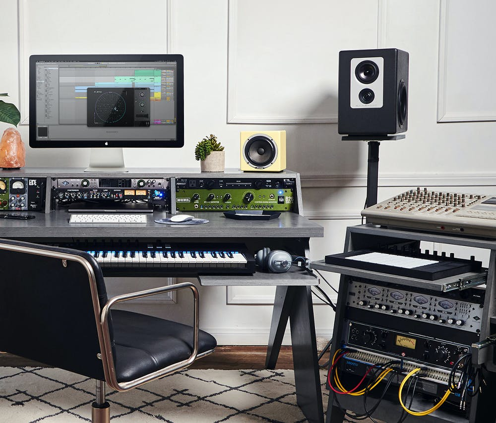 Studio setup with grey Output Platform desk, grey Output Sidecar accessory to hold preamps and MIDI controller, studio monitors, and Apple desktop computer.