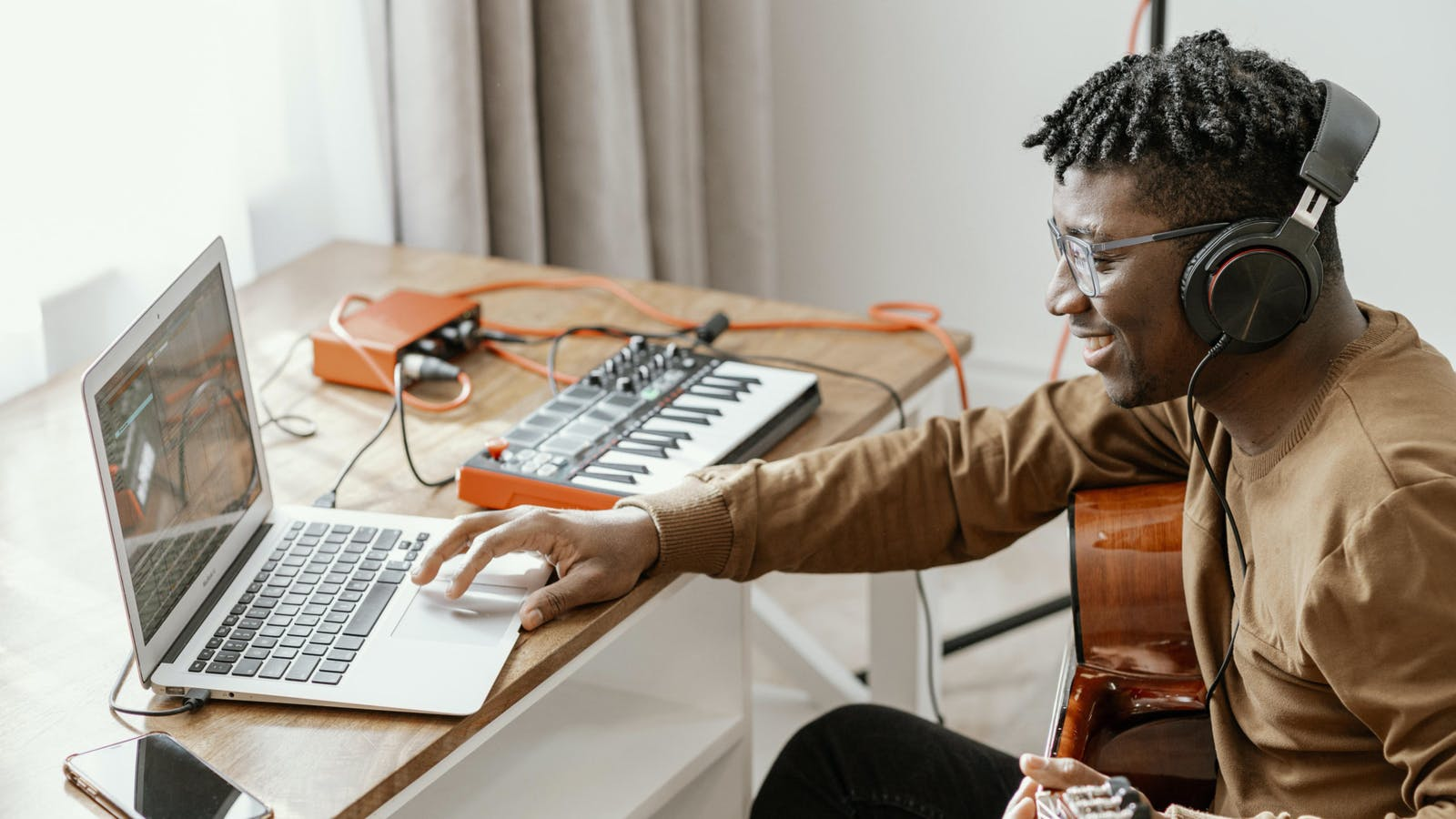 Man using music production software and playing guitar