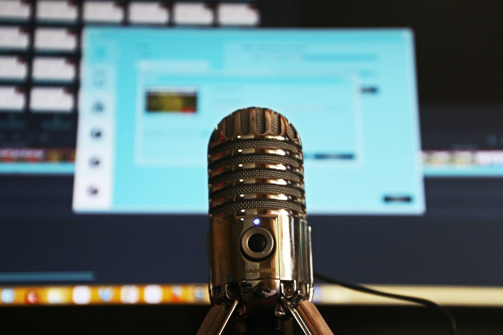 Gold microphone in studio in front of computer screen