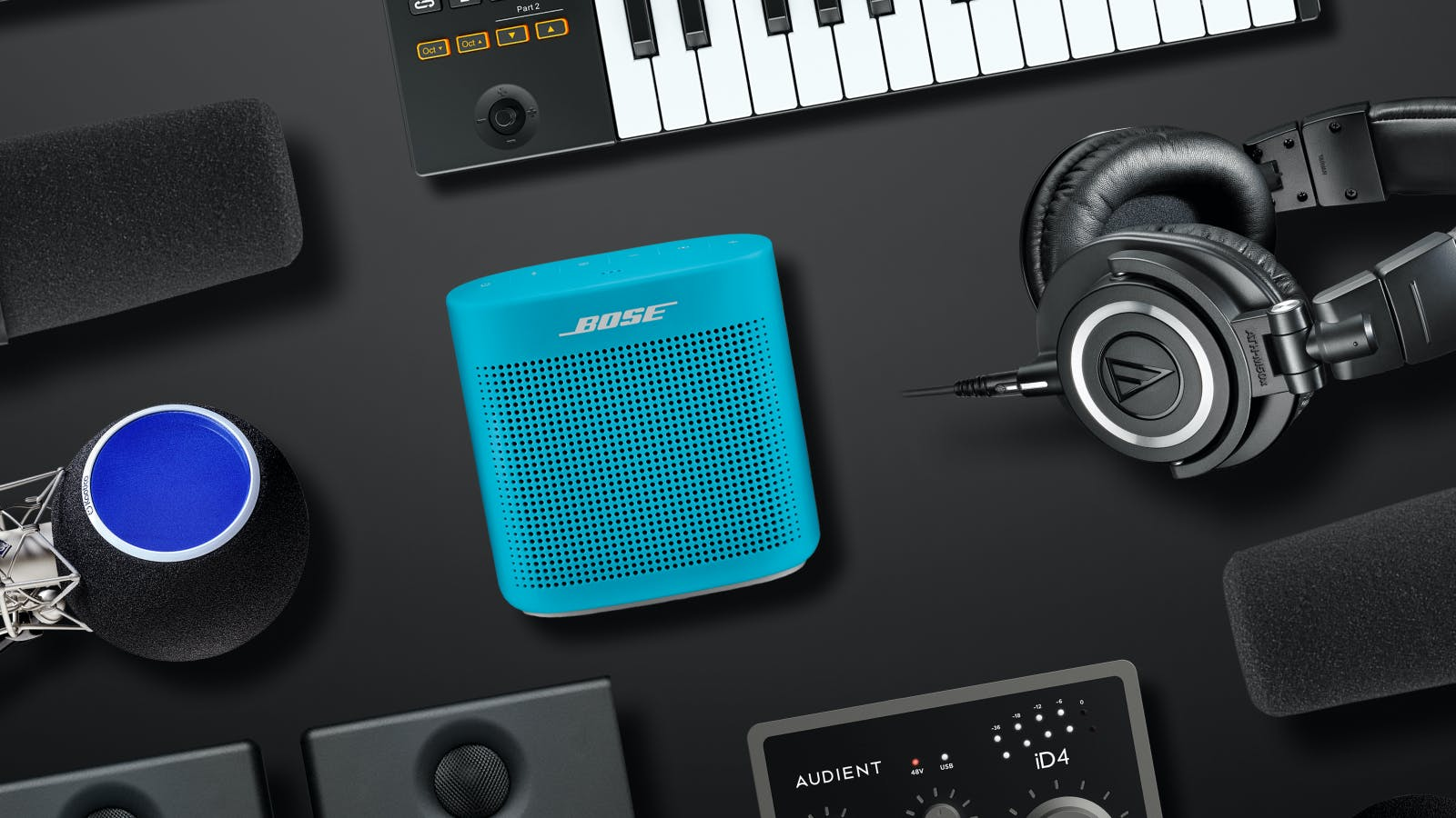 Small music studio gear including headphones, keyboards, and speakers